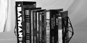 A black and white image of some books Looseleaf has worked on. Notables are Batman Black and White and leatherbound Elantris by Brandon Sanderson.